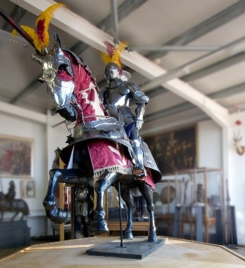 lot 512; comprising a life-size knight on horseback in tournament colours, charging with joust on horse at gallop in ornamental parade armour