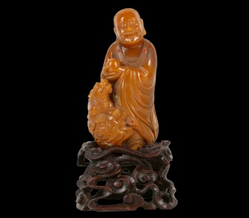 A CHINESE SOAPSTONE 'LUOHAN AND LION' GROUP, which sold for £32,400